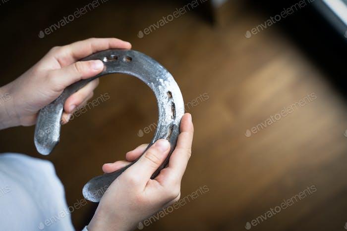 child holding a steel polished horshoe