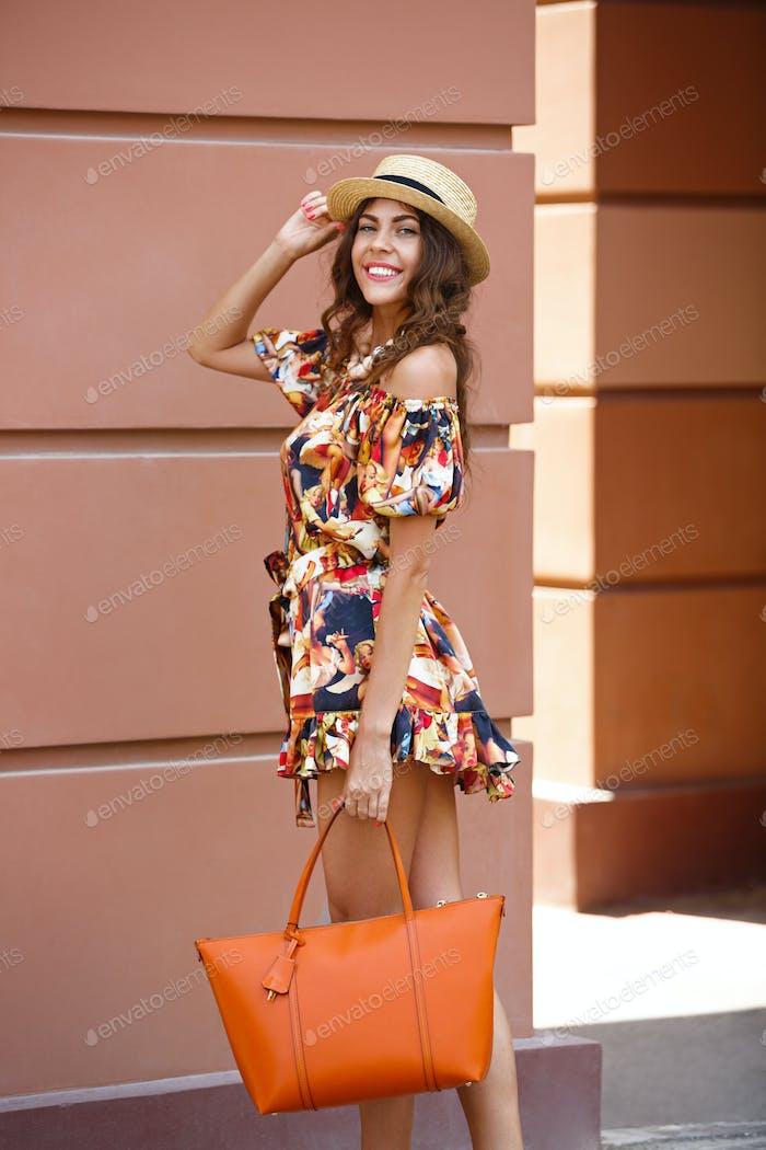 Stylish brunette girl dressed in short multi-colored dress and hat holding orange bag walks in the