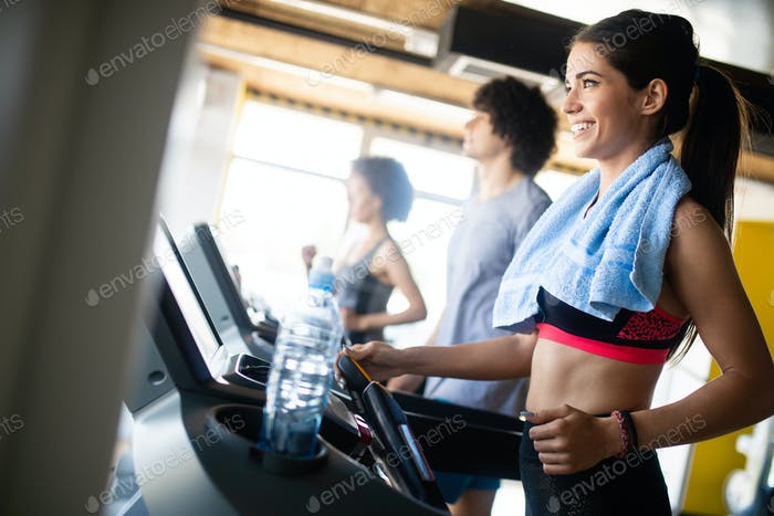 Happy fit Menschen laufen auf Laufband im Fitness-Fitness-Fitness-Fitness-Club