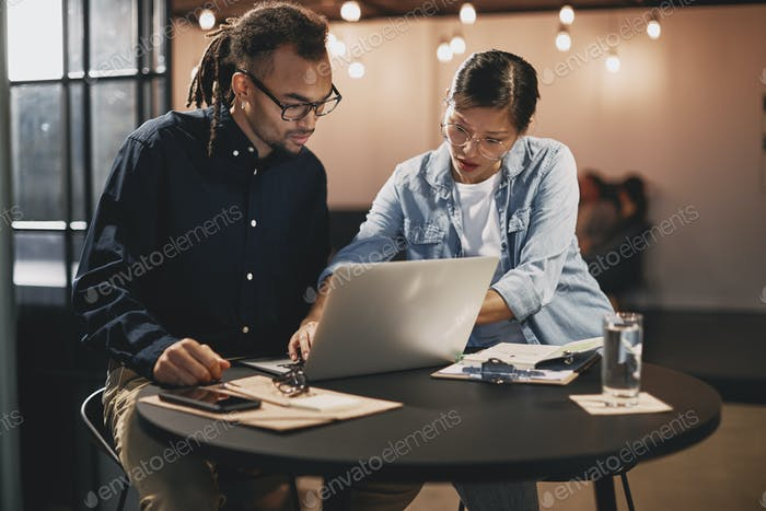 Businesspeople working together on a laptop at an office table
