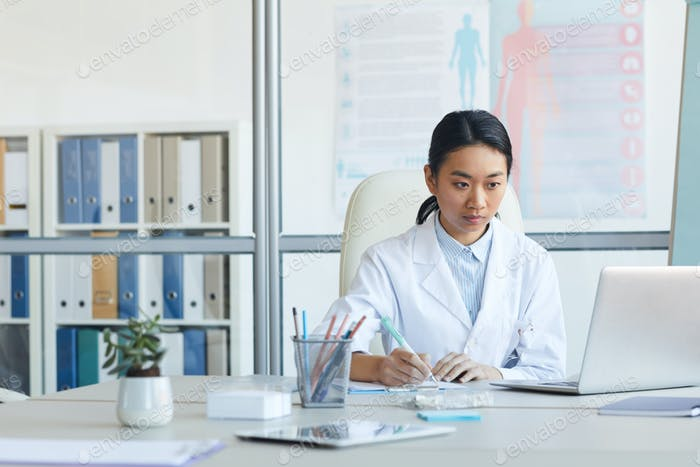 Young Female Doctor Using Computer