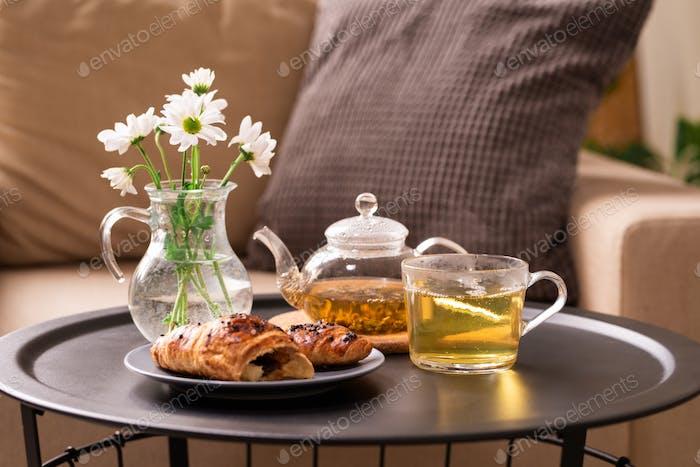 Frischer Kräutertee, hausgemachtes Croissant auf Teller und Glaskanne mit weißen Blüten