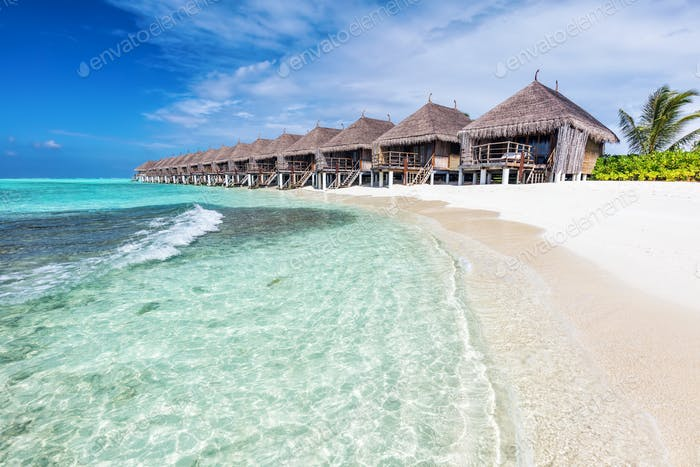 Water villas in a row by the seashore on Maldives Tropical resort