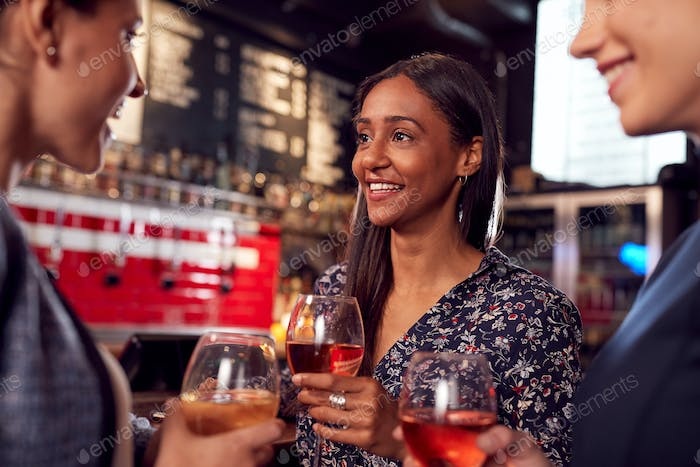 Three Women Meeting For Drinks And Socializing In Bar After Work