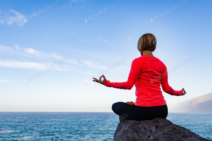 Woman meditating in yoga pose, ocean view