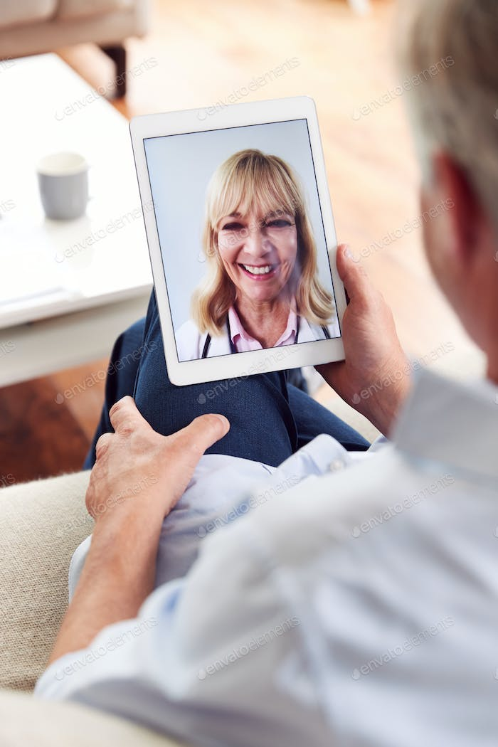 Mature Man Having Online Consultation With Female Doctor At Home On Digital Tablet