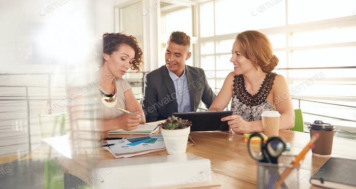 Image of three succesful business people using a tablet during a