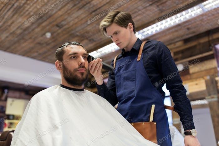 man and barber with trimmer cutting hair at salon