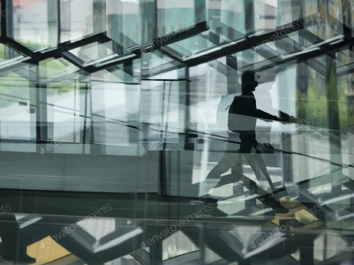 A man walking through the Harpa building, with glass walls and reflected light.