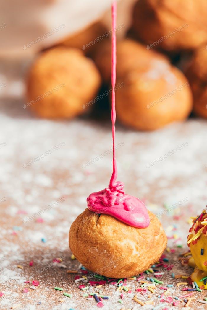 Pink glaze poured down on a little doughnut.