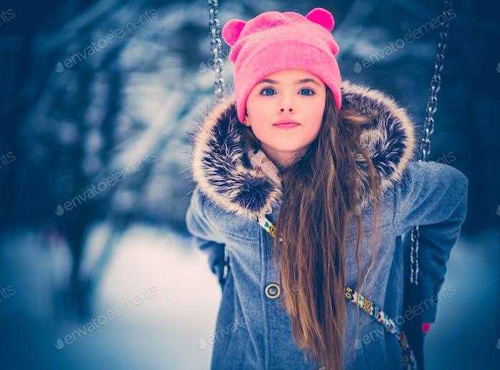 Charmantes kleines Mädchen auf Schaukel im verschneiten Winter