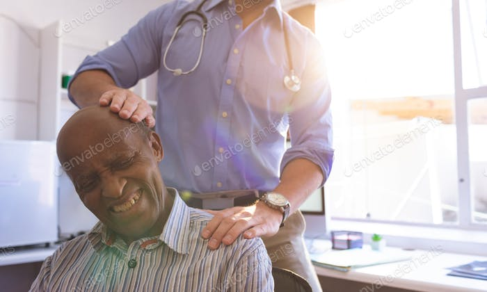 Front view of a Caucasian male doctor doing check up of an African senior man in clinic