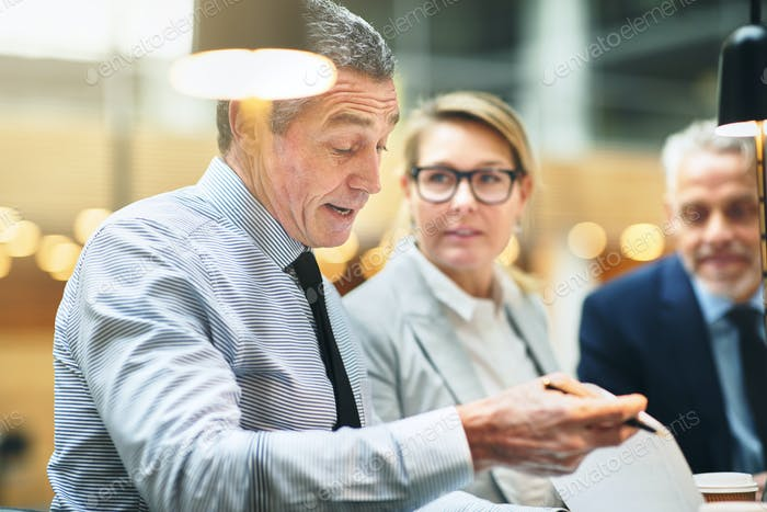 Mature executives discussing paperwork together during a meeting