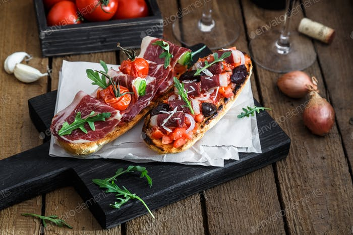 Tapas with slices jamon serrano, salami, olives and cheese on a wooden table