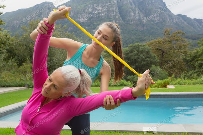 Caucasian female trainer assisting active senior Caucasian woman to exercise with resistance band