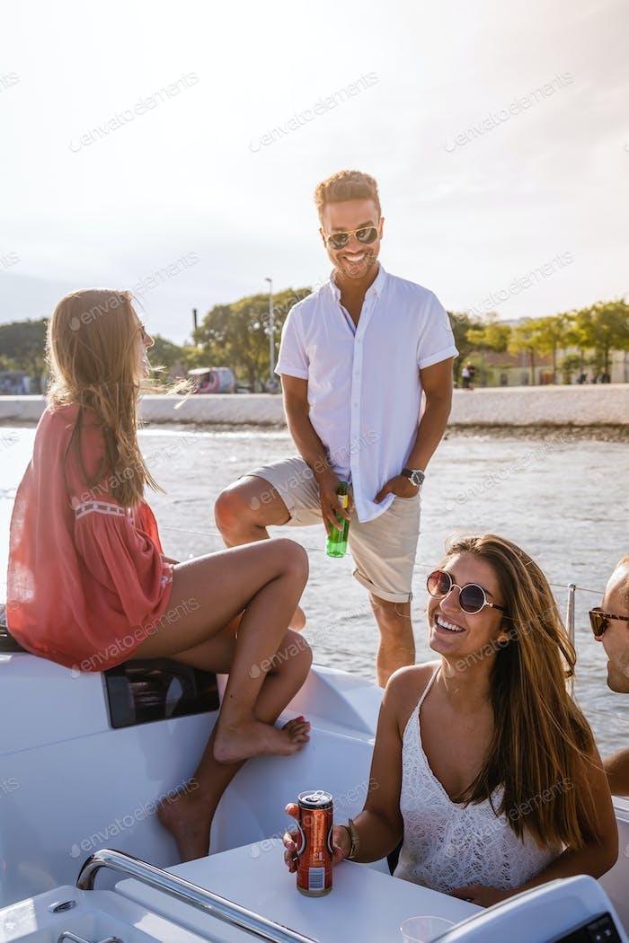 Group of friends having fun in boat in river