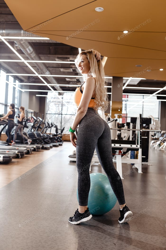 Slender blond girl with long hair dressed in a sportswear is posing next to the fitness ball in the