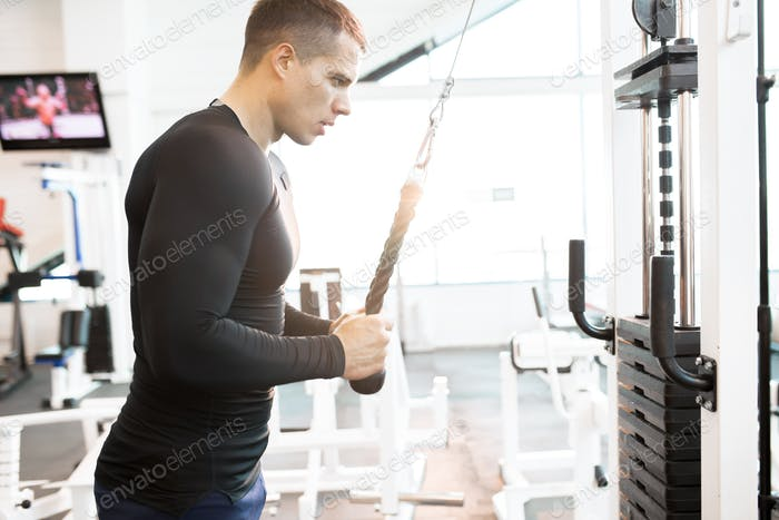 Muscular Man Working Out Using Machines