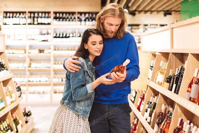 junge schöne paar verträumte Wahl Wein zusammen in superm
