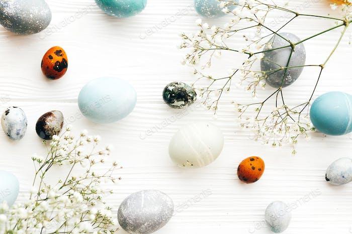 Stilvolle Ostereier mit Frühlingsblumen flach lag auf weißem Holzhintergrund