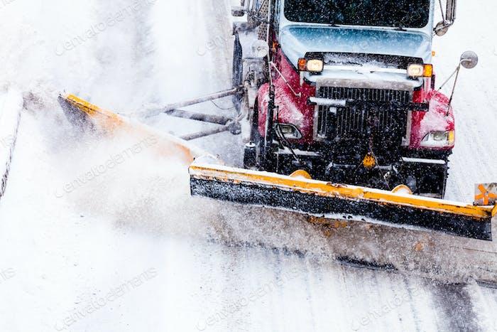 Schneepflug entfernt den Schnee von der Autobahn während eines Schneesturms