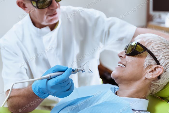 Laser Teeth Whitening. Mature Woman Sitting In Dentist Chair
