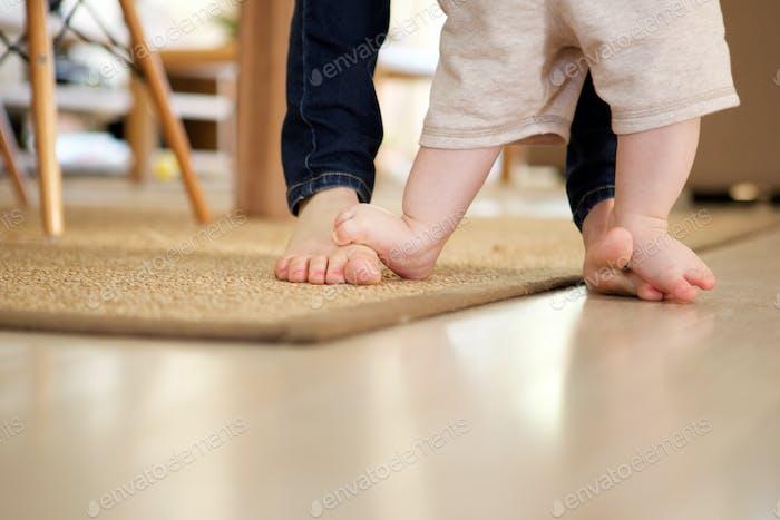 Mutter Lehre Baby zu Fuß drinnen