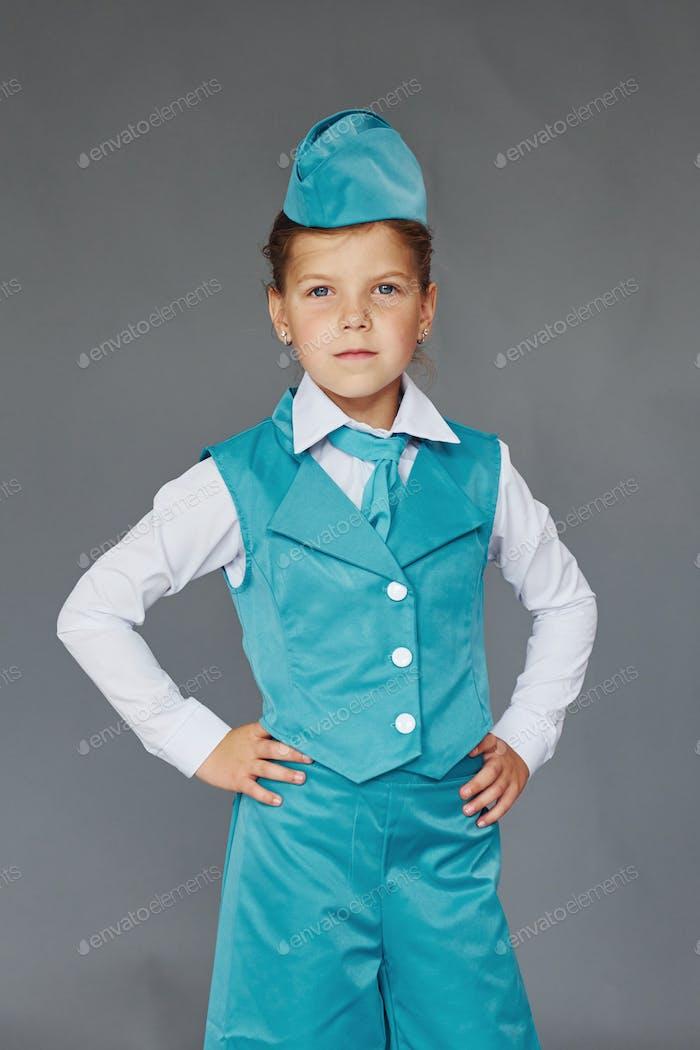 Cute little girl in blue stewardess uniform is posing for the camera