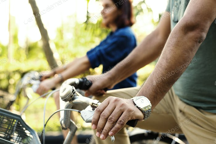 Couple riding bicycle together in jungle