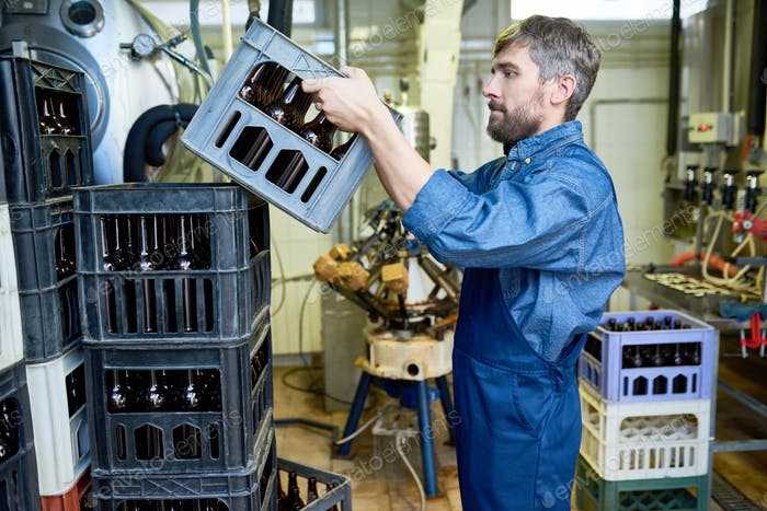 Serious bearded mover in uniform stacking boxes with beer bottle