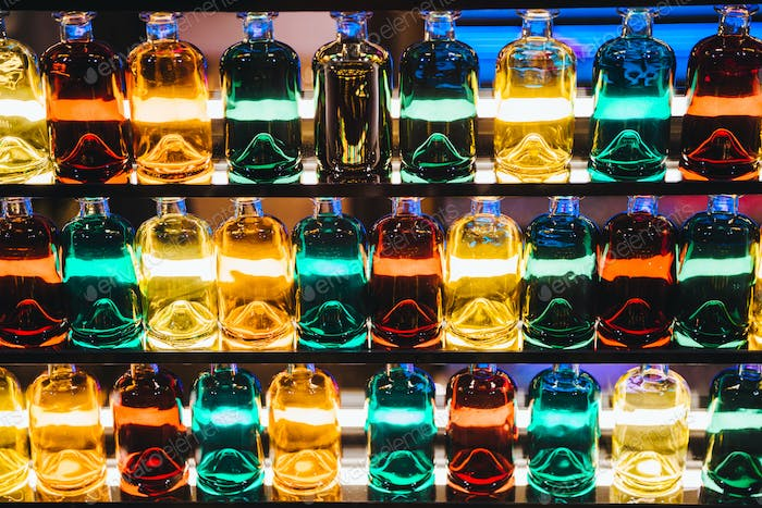 Background with different colored bottles placed on illuminated shelves