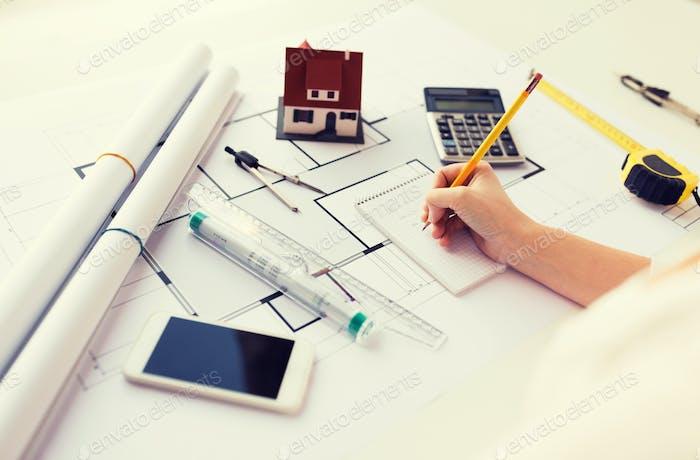 Nahaufnahme der Hand auf Blueprint Schreiben auf Notizbuch