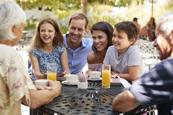 Multi Generation Family Enjoying Snack At Outdoor CafŽ Together