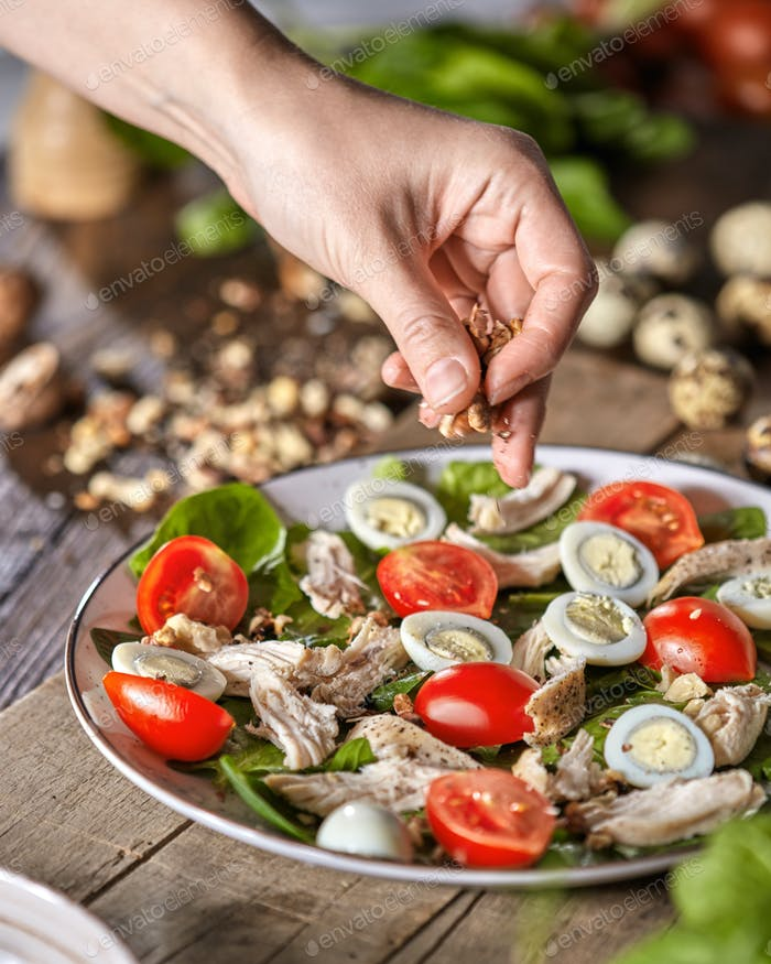 Female hand puts walnuts to the plate of freshly cooked salad from natural ingredients on a wooden