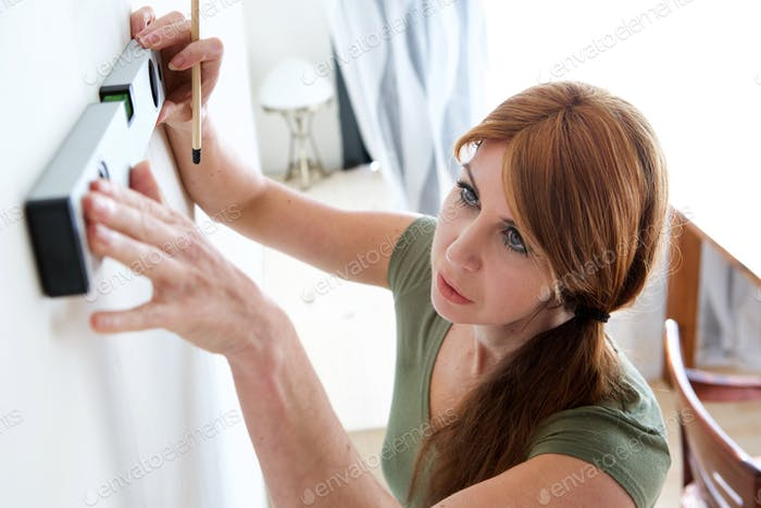 Mature woman marking on wall with level