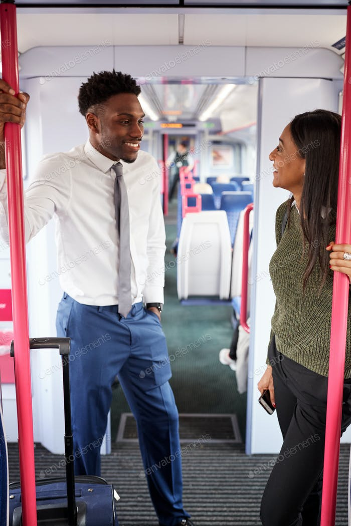 Business Passengers Standing In Train Commuting To Work Having Discussion