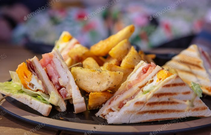 Club sandwich, take away food. Toasted bread slices, cheese, ham, egg, lettuce,