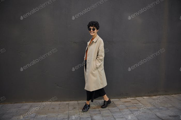 Outdoor shot of happy young pretty female with short haircut walking along black urban wall