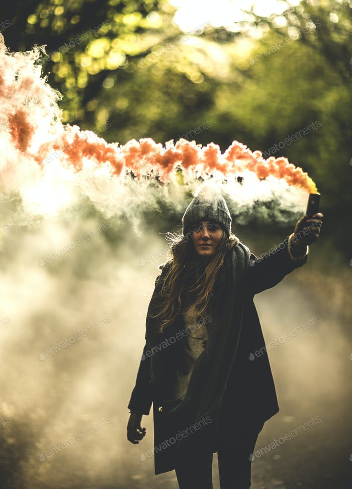 A young woman waving an orange smoke flare in a forest.