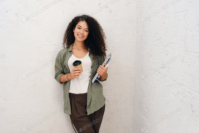 Pretty smiling woman in khaki shirt holding notepads and coffee happily looking in camera