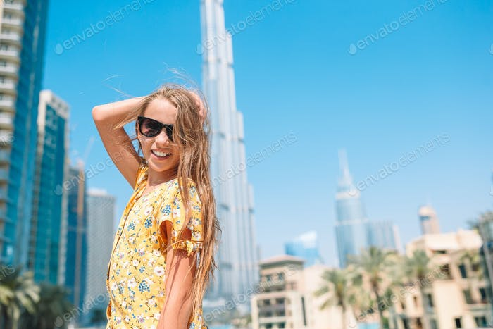 Happy girl walking in Dubai with skyscraper in the background