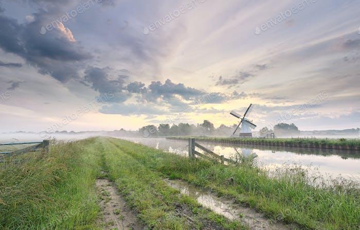 hermosa mañana sobre encantador molino de viento por río