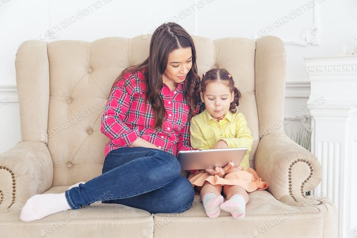 Mother with children learning computer tablet