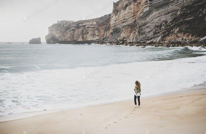 Woman tourist walking at Atlantic ocean beach in Portugal