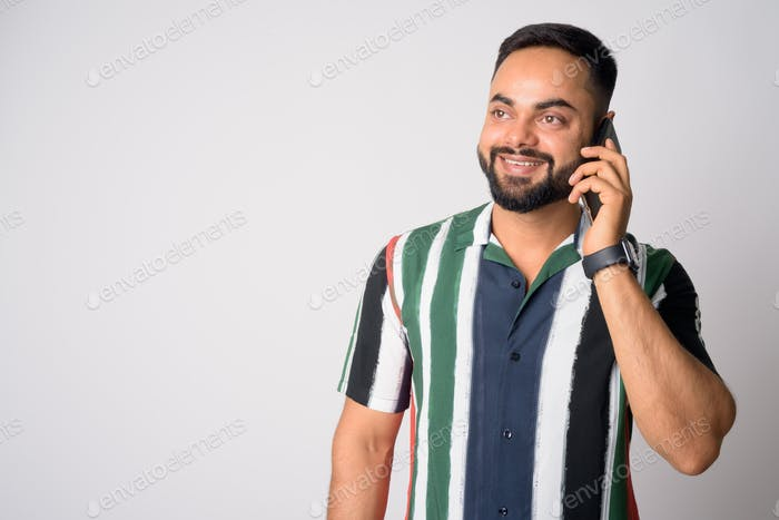 Portrait of happy young bearded Indian man talking on the phone