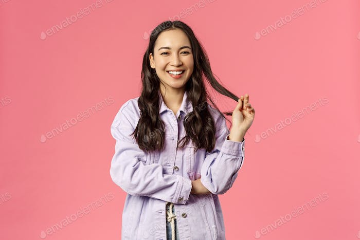 Portrait of cheerful pretty korean woman in denim jacket, roll strand of hair with fingers, giggle