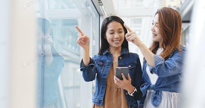 Chicas amigas comprobando horarios en el teléfono móvil en el aeropuerto de Hong Kong