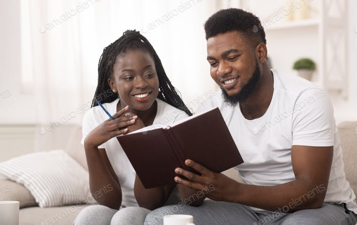 Afro couple looking at notepad at home, checking plans and to-do-list
