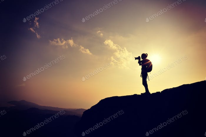 Woman photographer on sunset mountain peak