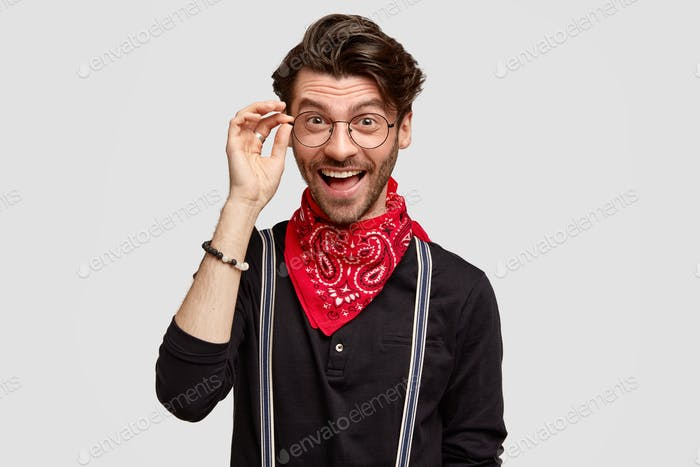 Happy male hipster being glad to meet with friends with common interests, wears spectacles and styli